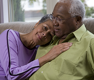 Senior couple embracing on couch.